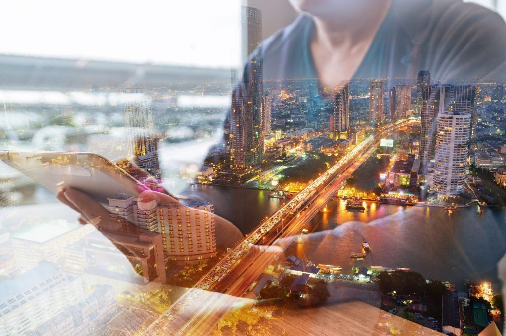 Man checks finances on table, superimposed over photo of a city